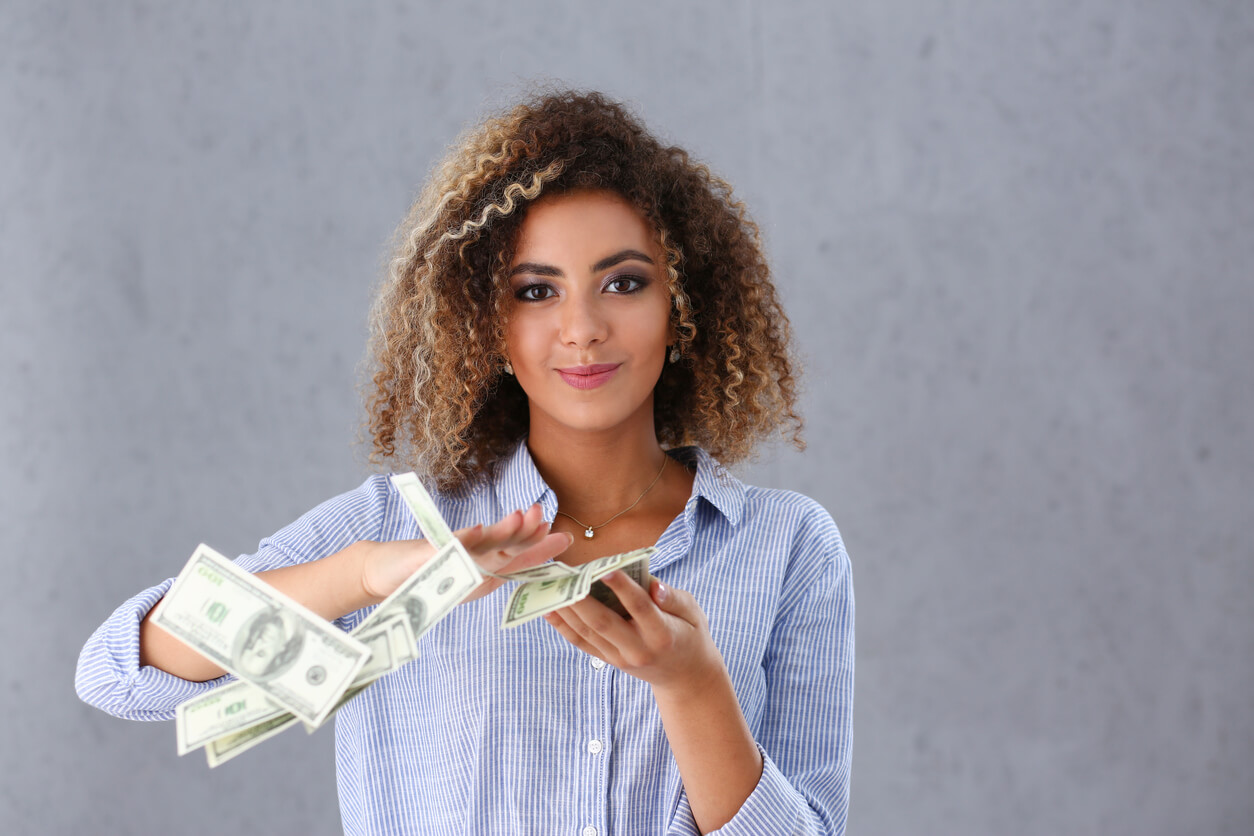 Confident woman counting money for down payment.