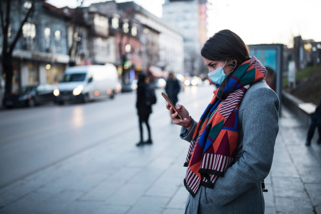 woman wearing surgical mask standing on street looking at phone during pandemic