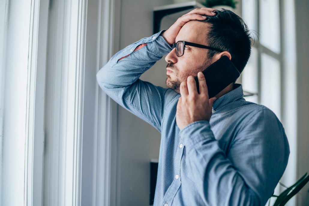 man stressed talking on phone looking out window